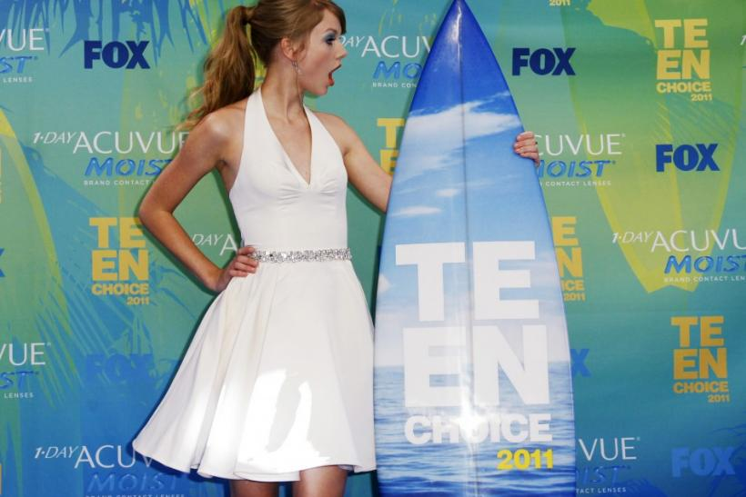 Singer Taylor Swift poses in the press room with her award backstage at the Teen Choice Awards in Los Angeles