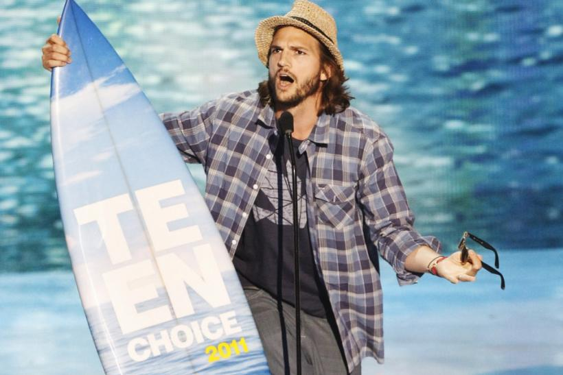 Actor Ashton Kutcher sings as he accepts the Choice Movie Actor: Romantic Comedy award at the Teen Choice Awards at the Gibson amphitheater in Universal City, California