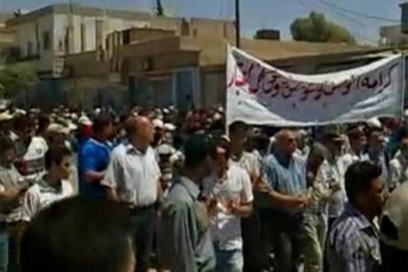 Protesters march while holding banners in Qamishli, northeast Syria