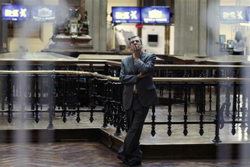 A trader is seen through a window as he looks at screens at the bourse in Madrid
