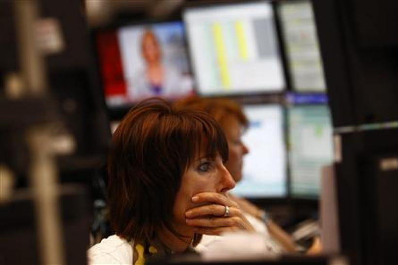 Traders work at their desks at Frankfurt's stock exchange