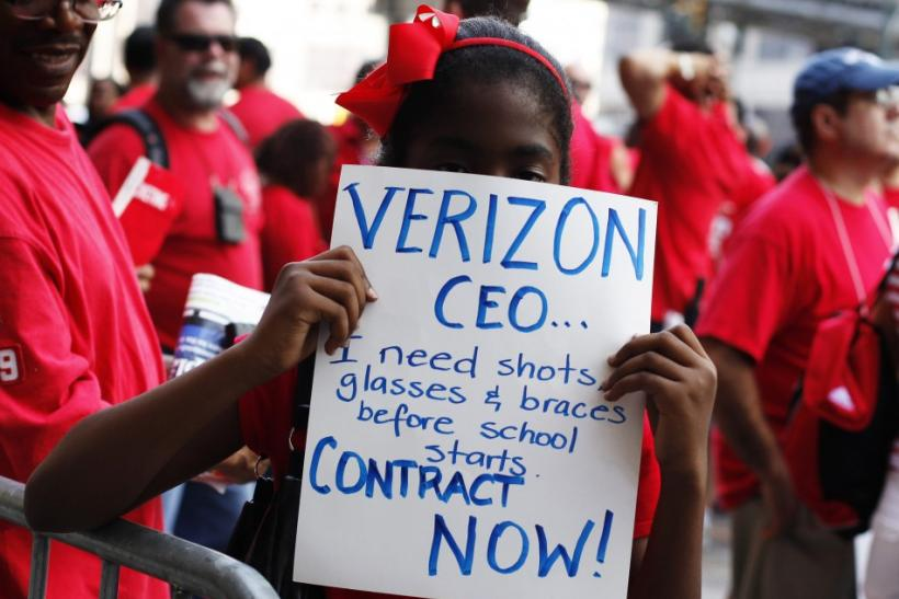 A girl holds a sign as workers rally outside the Verizon headquarters in New York