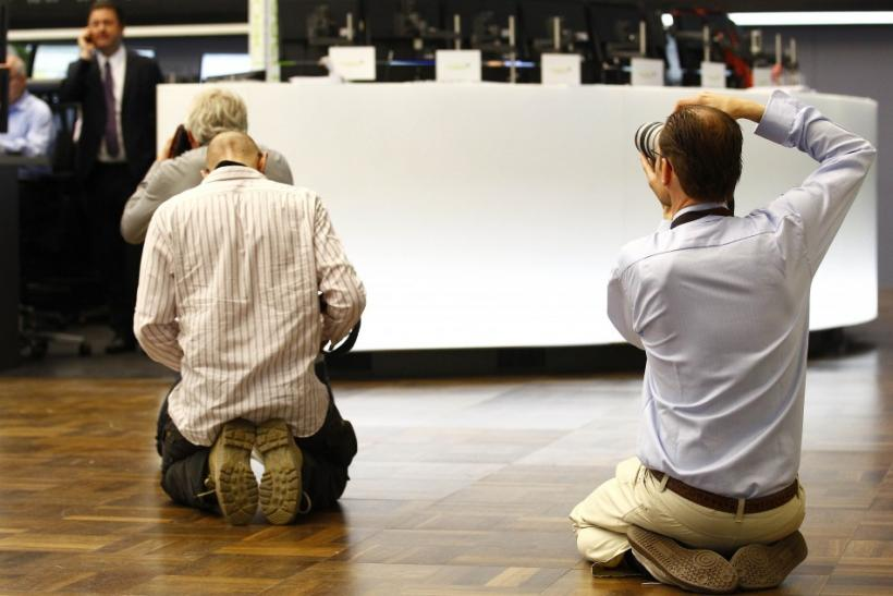 News photographers take pictures of share traders reacting on early morning trading at Frankfurt's stock exchange