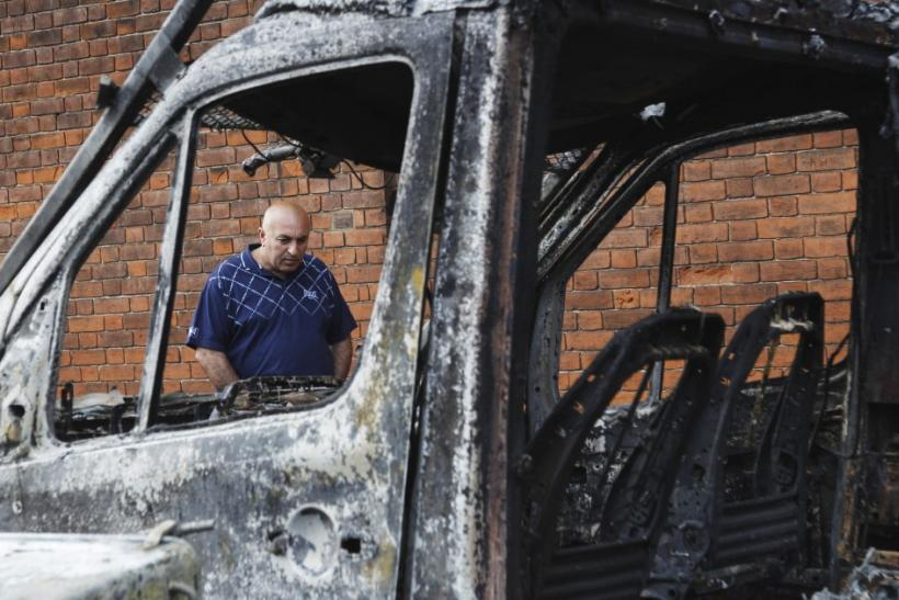 A man looks at a burned out police van set alight during riots in Tottenham