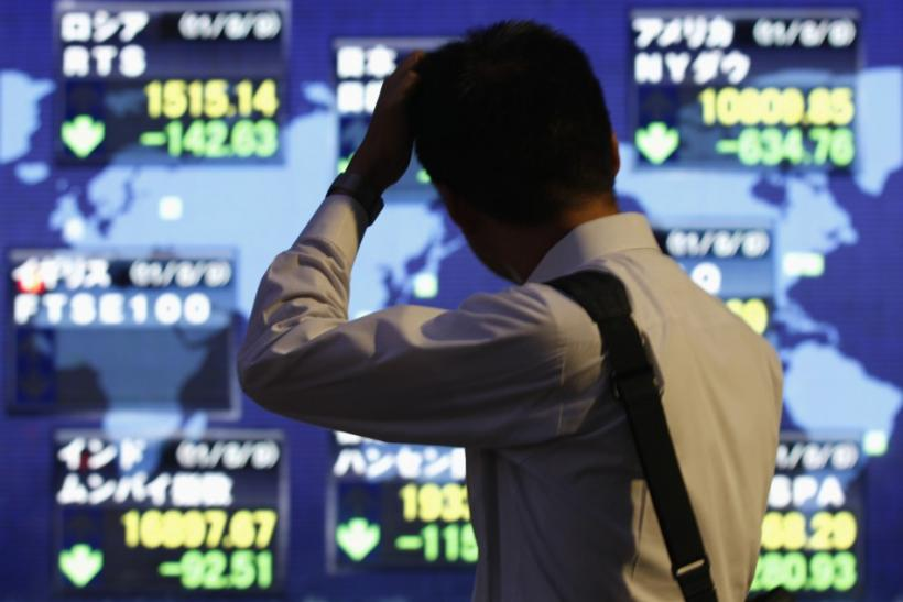 A man scratches his head in front of an electronic board displaying falls in major market indices around the world, outside a brokerage in Tokyo