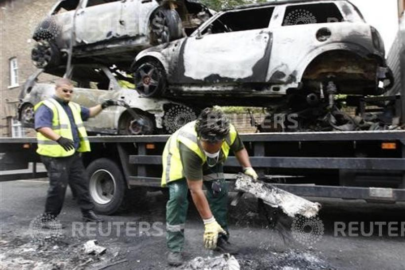 Council workers clear the remains of destroyed vehicles in Hackney, north London