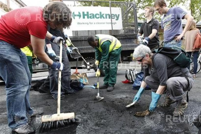 Part of a group of about 300 volunteers help clear the remains of destroyed vehicles in Hackney
