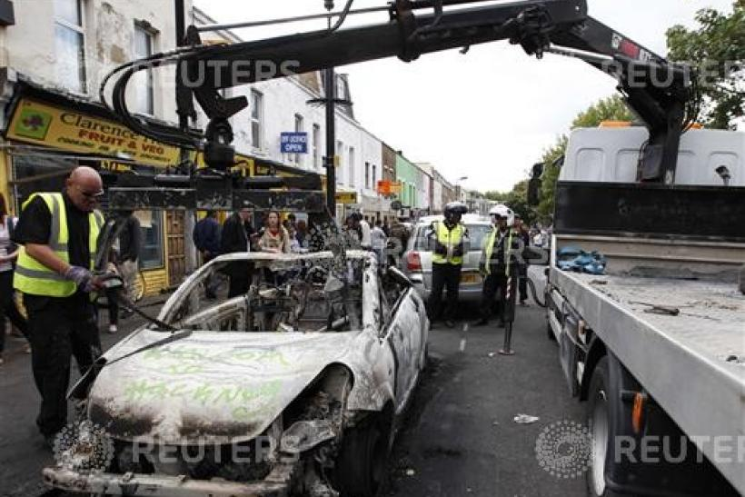 A council worker removes a destroyed vehicle in Hackney, north London