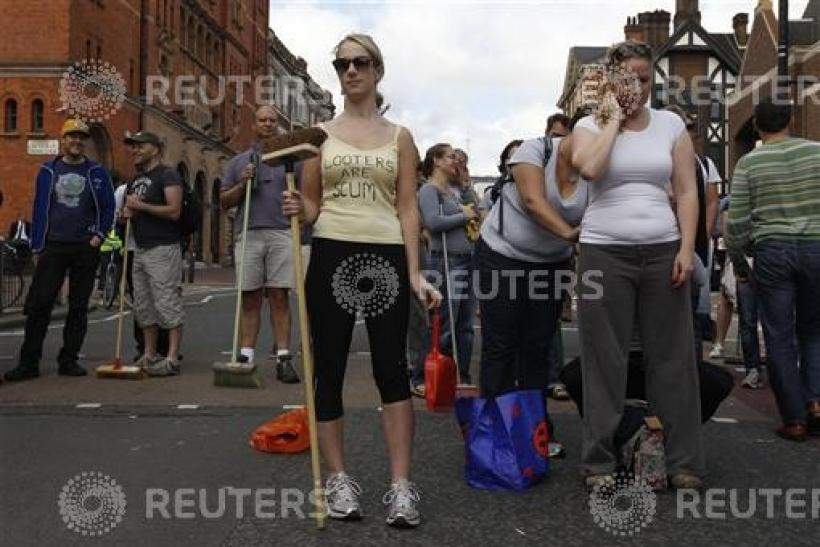 A woman poses for a photograph as volunteers wait to clear-up after overnight disturbances in Clapham Junction, in south London