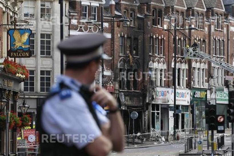 A police officers stands near a burnt out shop in Clapham Junction, in south London