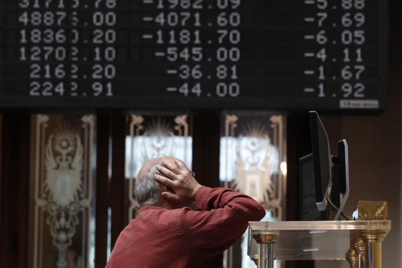 A trader stands in front of screens at the bourse in Madrid