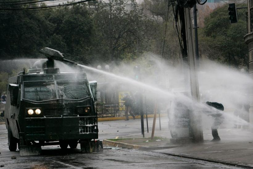 Riot policemen use a water cannon on student protesters in Santiago, Chile.