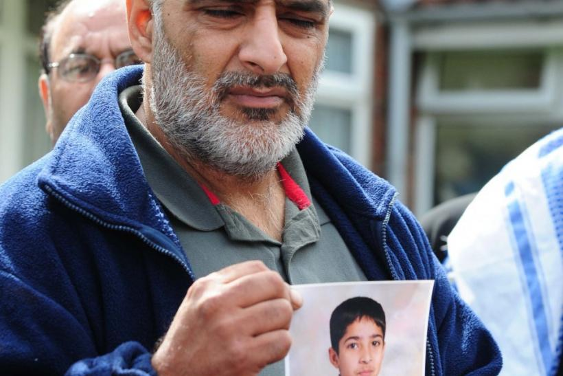 Tarmiq Jahan holds a picture of his son Haroon Jahan after he was killed killed by a car along with two other men in the Winson Green area of Birmingham