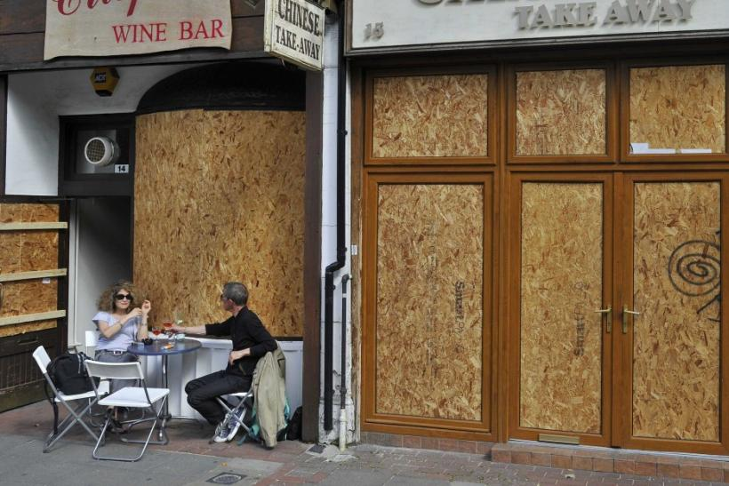 A couple drink at a boarded up wine bar in Ealing, west London