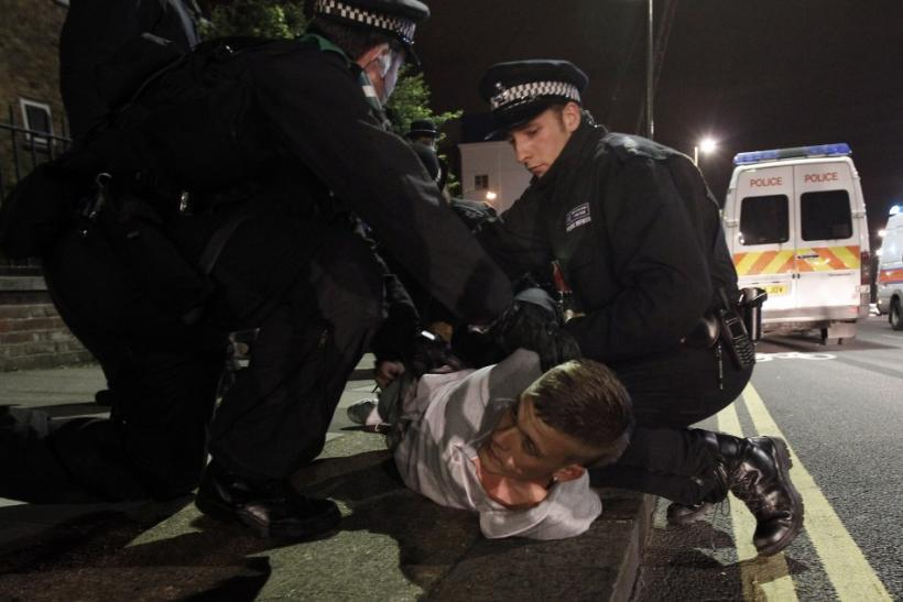 Police officers detain a man in Eltham, south London August 10, 2011.