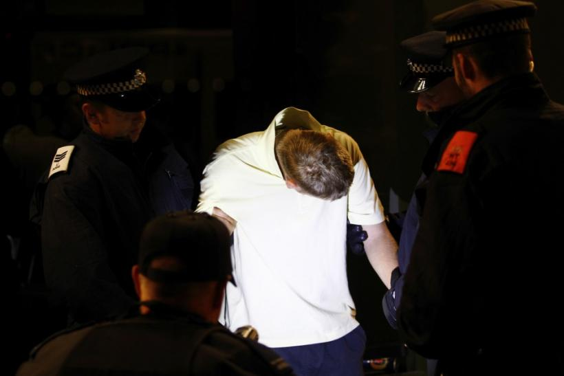Police officers restrain a man, who was part of a group that gathered to repel possible rioters and looters, as he struggles to avoid having his picture taken in Eltham, southeast London, August 10, 2011