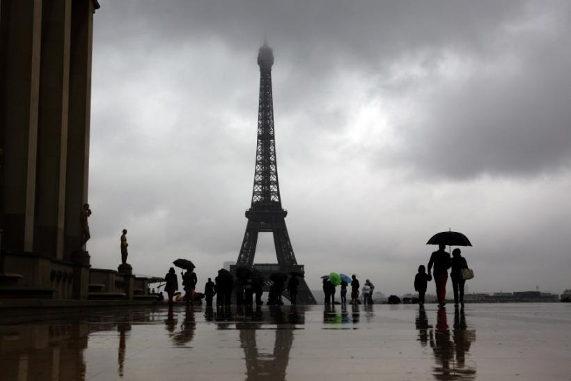 Tourists protect themselves from the rain under umbrellas in front of the Eiffel tower in Paris as they visit the French capital during summer holidays