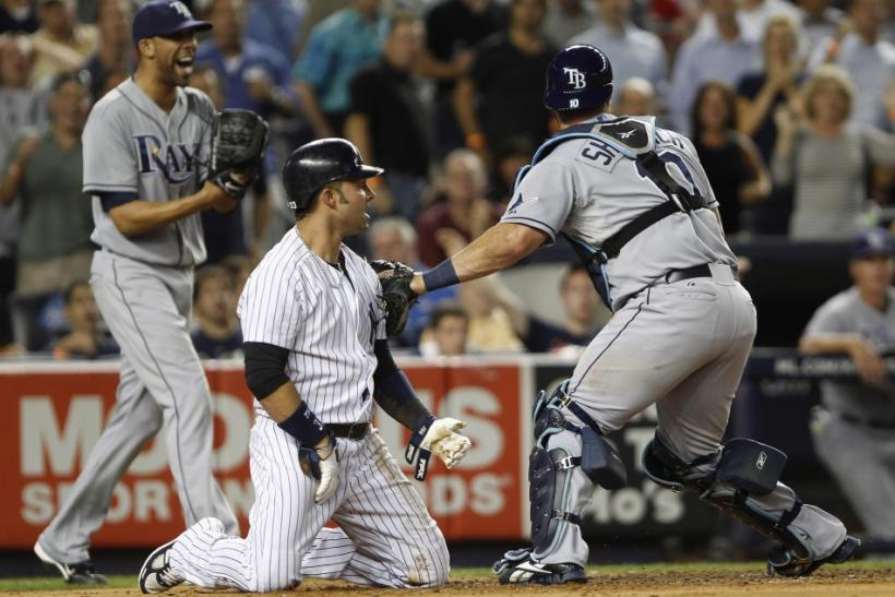 New York Yankees Nick Swisher reacts to being tagged out at home by the Tampa Rays catcher Kelly Shoppach in New York