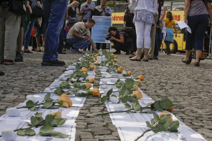 Roses are placed on sheets of paper with the names of those killed while trying to escape from East Berlin by crossing the Berlin Wall during a ceremony at the Brandenburg Gate in Berlin