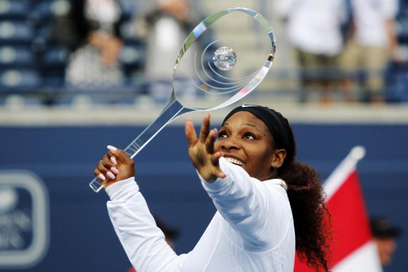 Williams of the US pretends to use the trophy as a tennis racket after defeating Stosur of Australia during their finals match at the Rogers Cup women's tennis tournament in Toronto