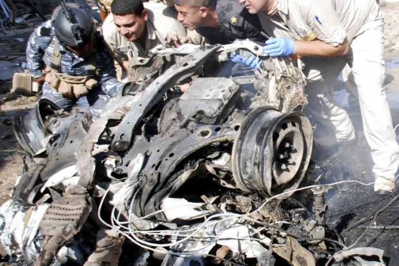 Security personnel remove the remains of a vehicle used in a bomb attack from the blast area in Kut