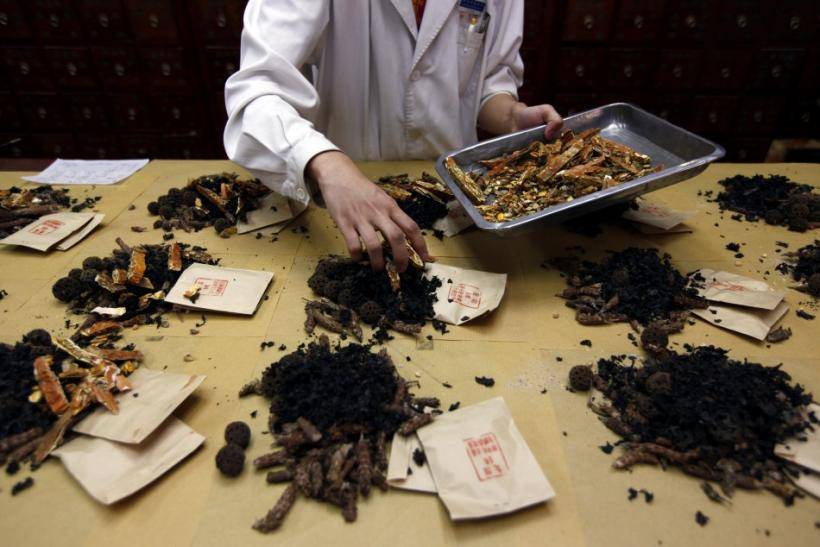 A worker prepares traditional Chinese herbal medicines at Beijing's Capital Medical University Traditional Chinese Medicine Hospital