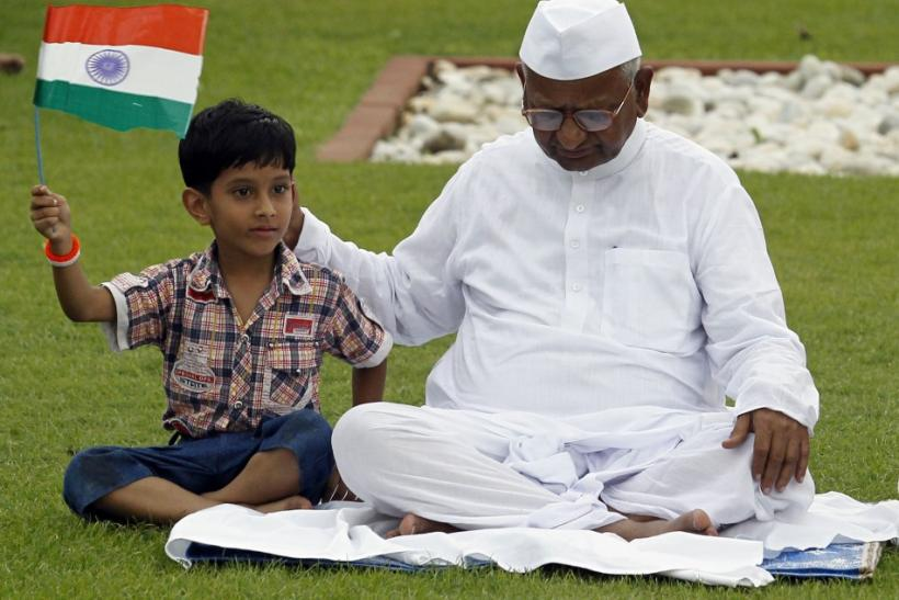 Boy holds Indian national flag as he sits next to veteran social activist Hazare at Mahatma Gandhi memorial at Rajghat in New Delhi