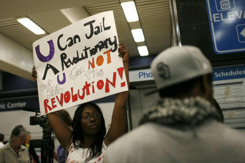 A protester holds up a sign on a BART train during a demonstration at the Civic Center Station in San Francisco