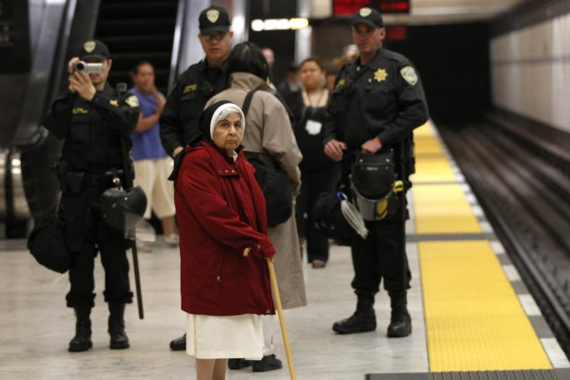 A nun waits for a train as police are pictured on the platform during a demonstration at the BART Civic Center Station in San Francisco