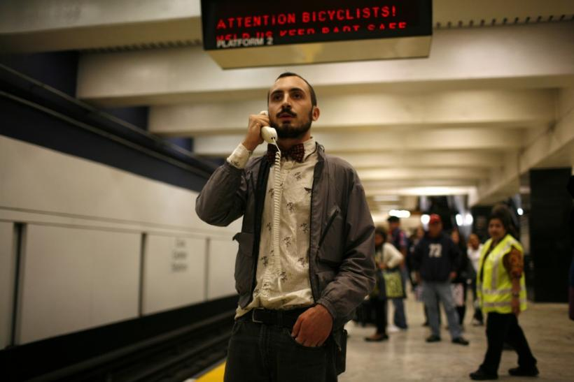 A protester talks on the detached handset of a telephone during a demonstration at the BART Civic Center Station in San Francisco