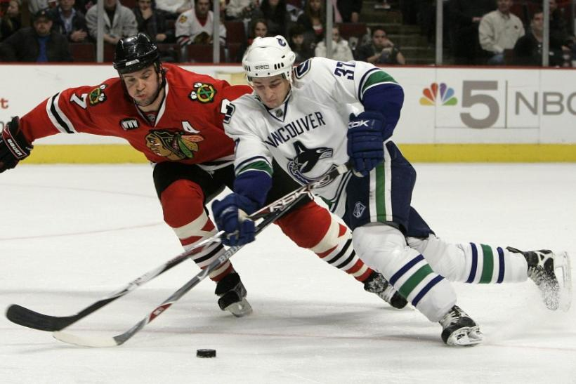 Vancouver Canucks' Rypien battles Chicago Blackhawks' Seabrook for the puck in the second period of their NHL game in Chicago