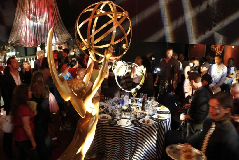 An Emmy statuette is pictured in the foreground as members of the media photograph the table setting and theme, mod illusions for the 2011 Creative Arts and 63rd Primetime Emmy Awards Governors Ball, during a press preview in North Hollywood, California