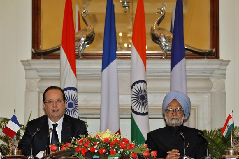 France's President Francois Hollande (L) speaks with the media as India's Prime Minister Manmohan Singh looks on after the signing of agreements ceremony in New Delhi February 14, 2013