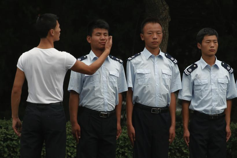 A man slaps the face of a firefighter as he stands in a line with colleagues during an inspection in central Beijing
