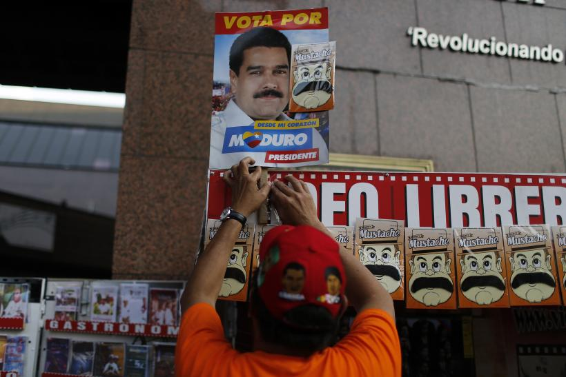 A street vendor arranges a picture of Venezuela's acting President and presidential candidate Nicolas Maduro above a row of fake moustaches in Caracas