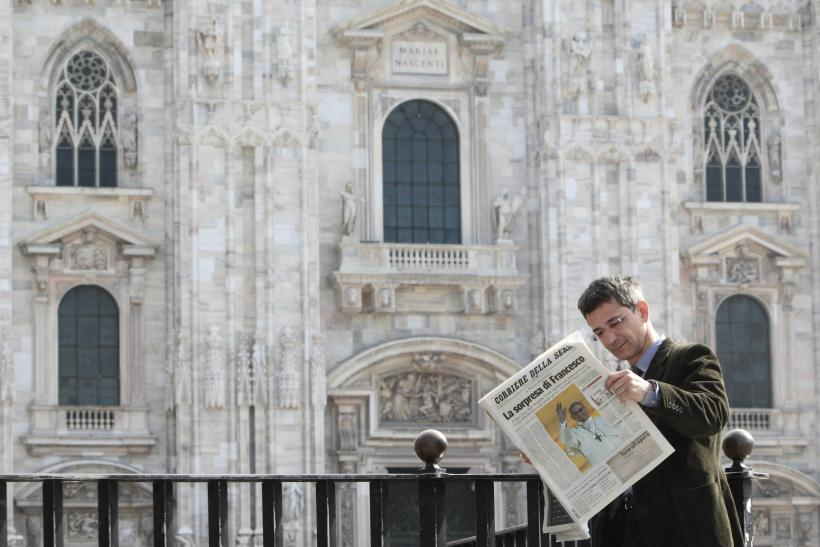 A man reads an Italian newspaper in Duomo square in downtown Milan.
