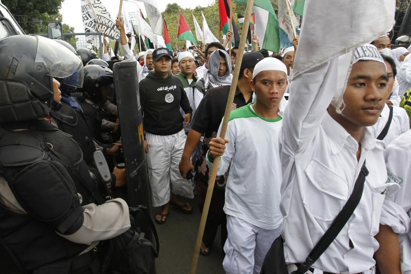 Riot police stand guard as members of the Islamic Defenders Front (FPI) hardline Muslim group take part in a pro-Palestinian rally outside the U.S. embassy in Jakarta