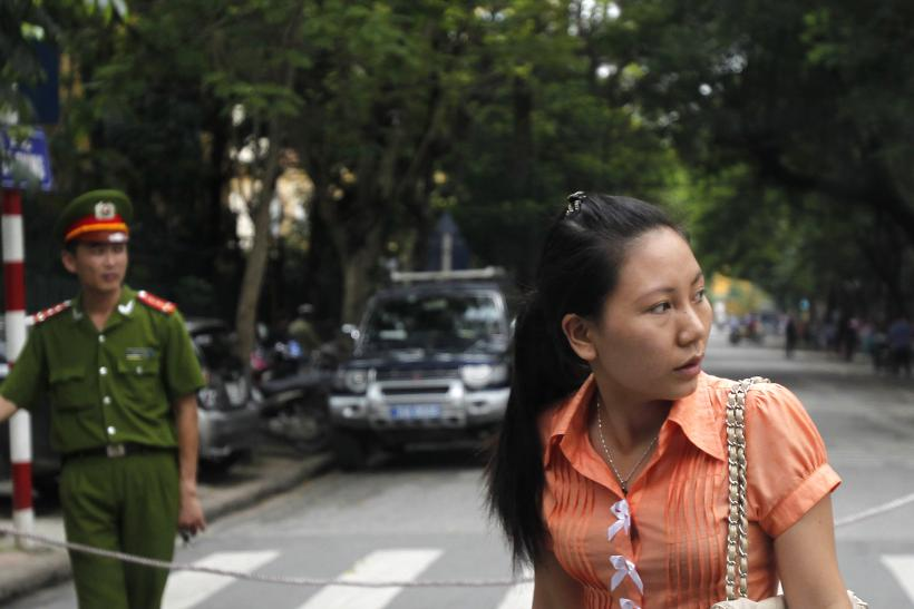 A plainclothes and a uniformed police officer stand in front of a court in Hanoi.