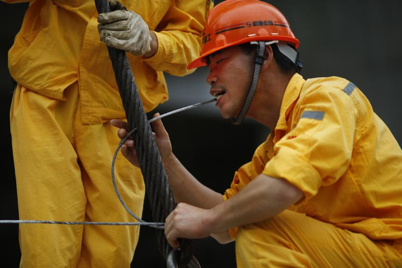 A constuction worker holds a steel cable with his teeth at the construction site.