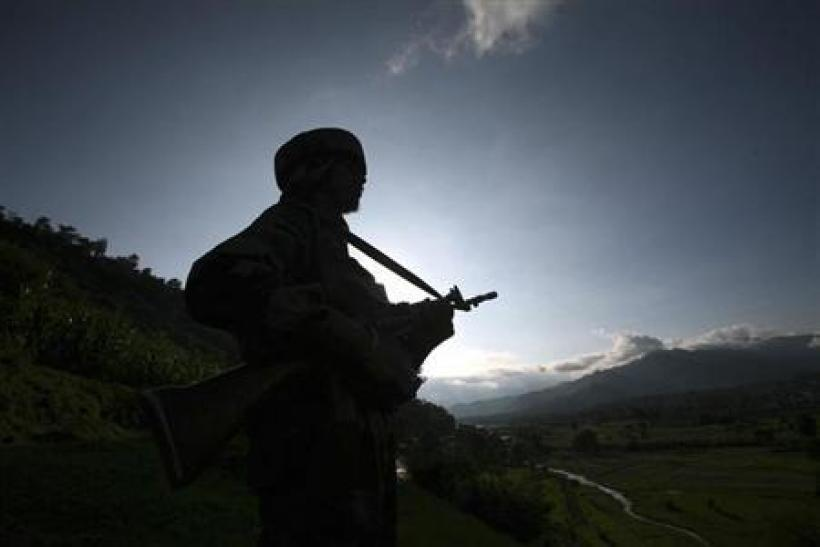 An Indian army soldier stands guard while patrolling near the Line of Control, a ceasefire line dividing Kashmir between India and Pakistan, in Poonch district