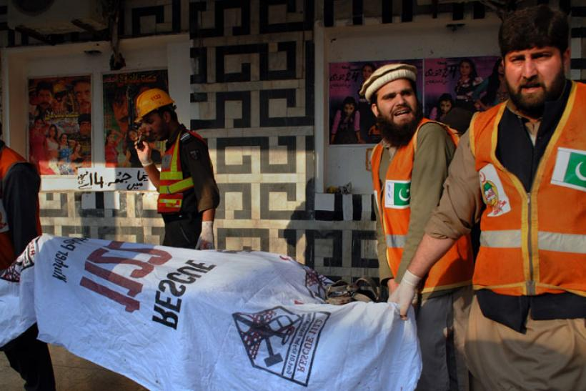 Rescue workers remove a body from the site of a grenade attack Shama movie theater in Peshawar, Pakistan