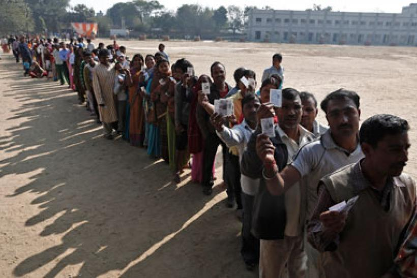 Voters queue at a polling station during the state assembly election in New Delhi on December 4, 2013.