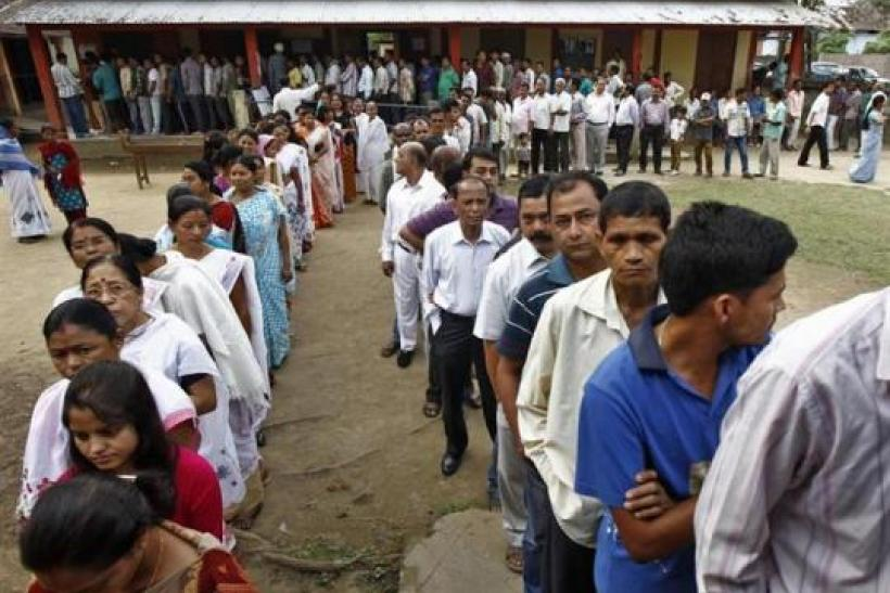 Voters line up to cast their vote outside a polling station in Nakhrai village in Tinsukia district, in Assam.
