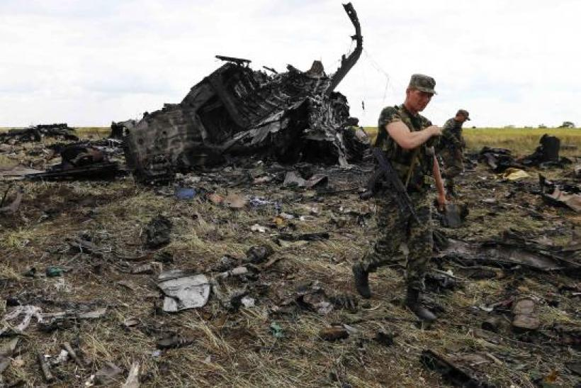 Pro-Russian separatists walk at the site of the crash of the Il-76 Ukrainian army transport plane in Luhansk, June 14, 2014. REUTERS/Shamil Zhumatov
