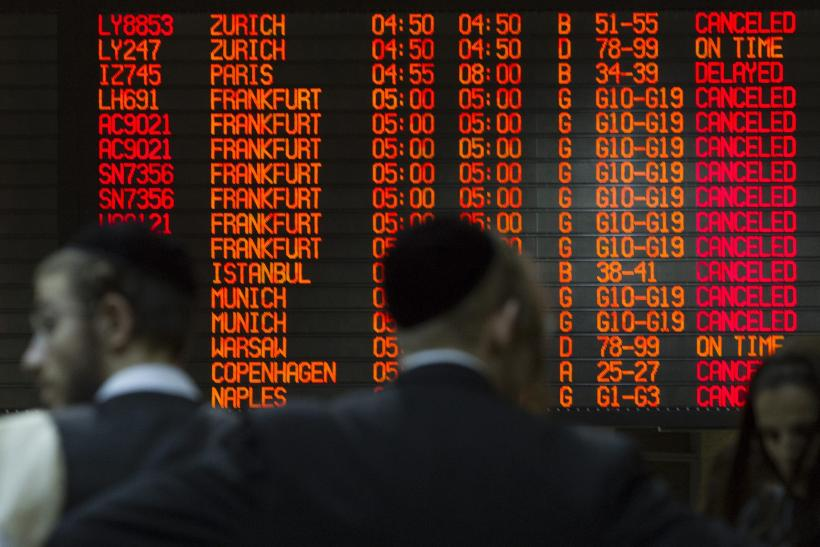 A departure time flight board displays various cancellations as passengers stand nearby at Ben Gurion International airport in Tel Aviv July 22, 2014.