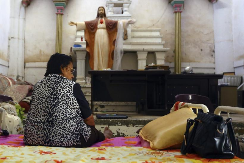 An Iraqi Christian woman fleeing the violence in the Iraqi city of Mosul, sits inside the Sacred Heart of Jesus Chaldean Church in Telkaif near Mosul, in the province of Nineveh, July 20, 2014