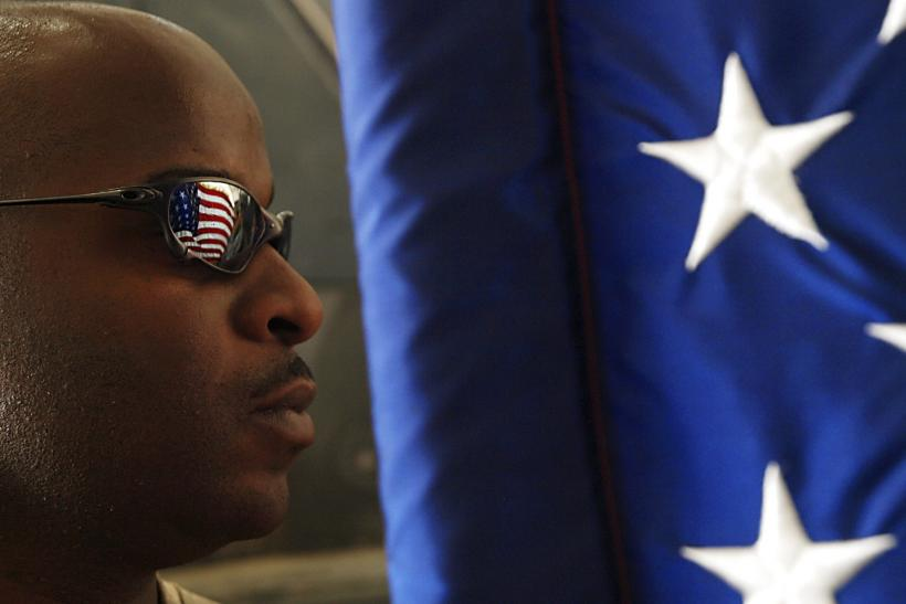 An African-American Soldier Stands Beside The U.S. Flag