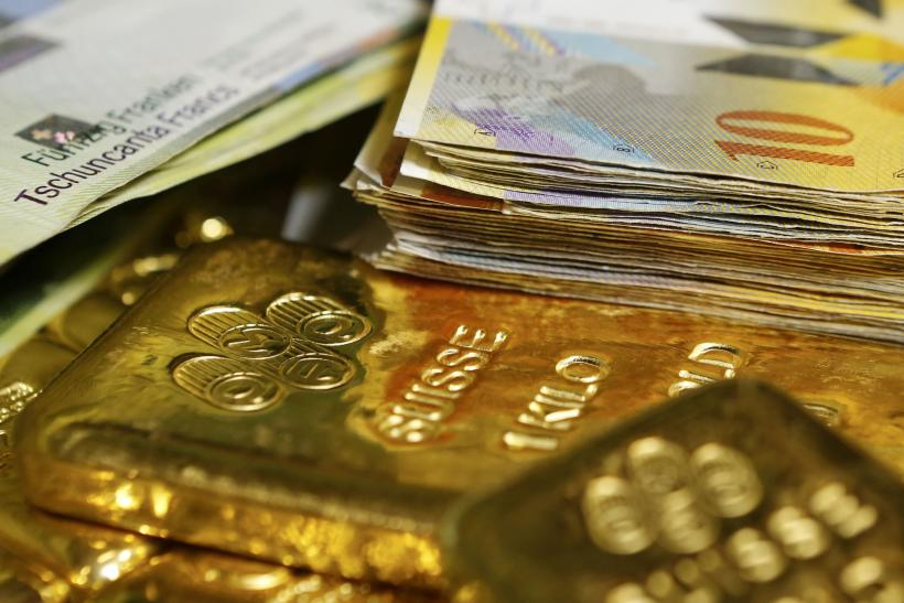 swiss franc banknotes and gold bars