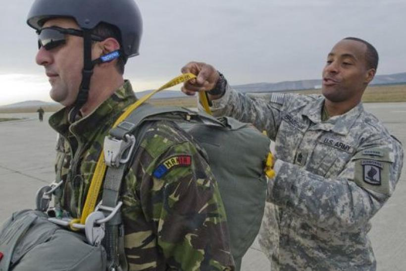 A U.S. soldier assists his Romanian counterpart