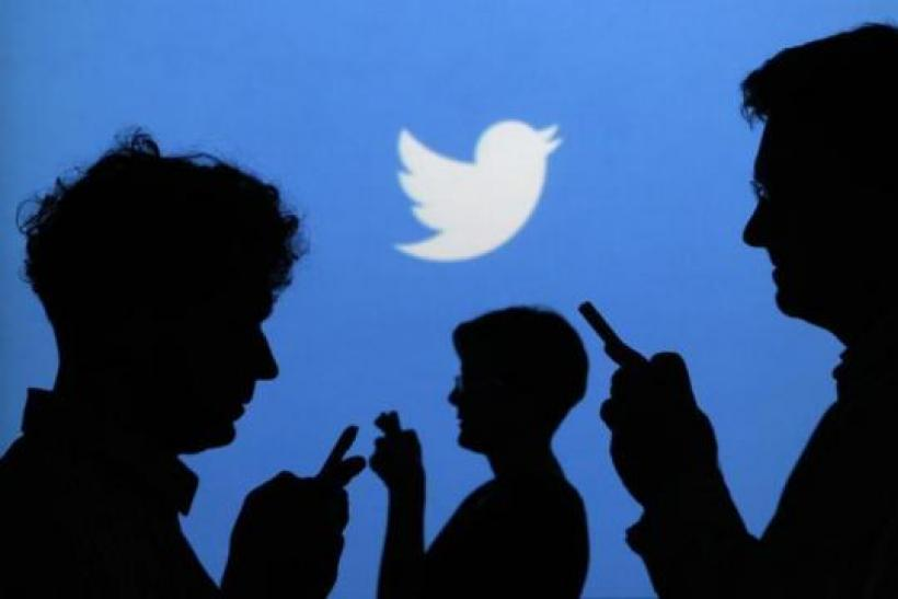 people-holding-mobile-phones-are-silhouetted-against-backdrop-projected-twitter-logo
